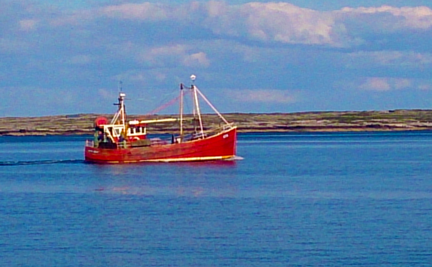 Small Aran fishing boat heading out to sea